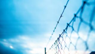 Barbed wire fence under blue skies