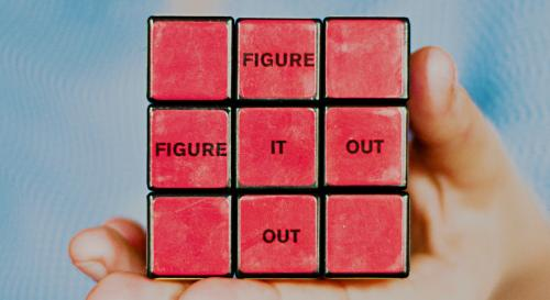 A red rubric cube that says 'figure it out' horizontally and vertically